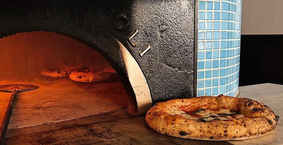 A baked pizza sitting on the hearth of a pizza oven that currently has two other pizzas in it.