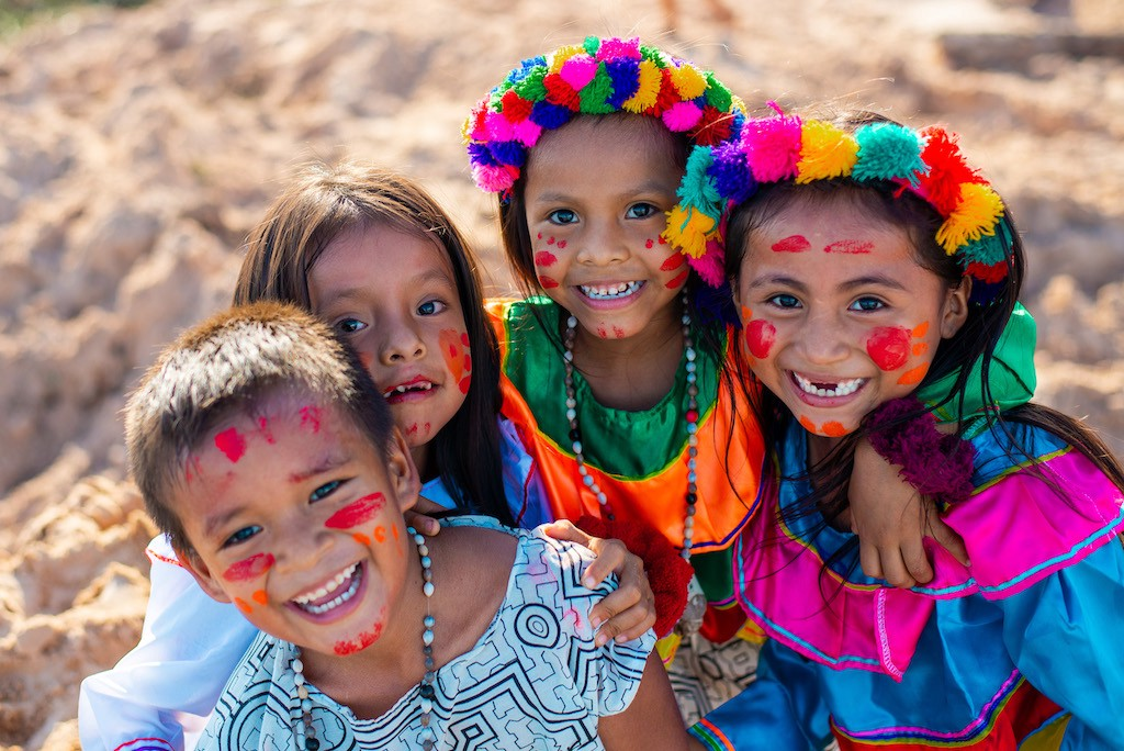 Four Shawi children with their arms around each other, wearing colourful traditional clothing and face paint.