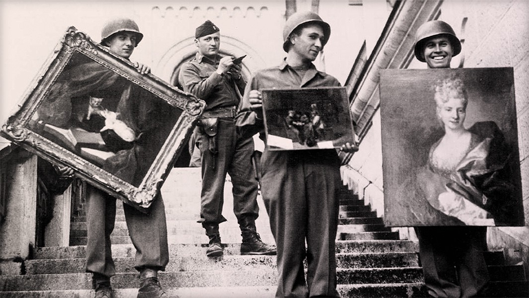 Four Monuments Men on the steps of a palace. Three are holding recovered artwork.