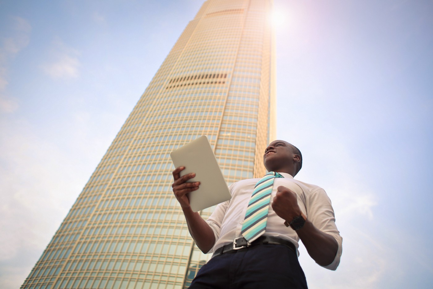 A business man standing in front of a high-rise building.