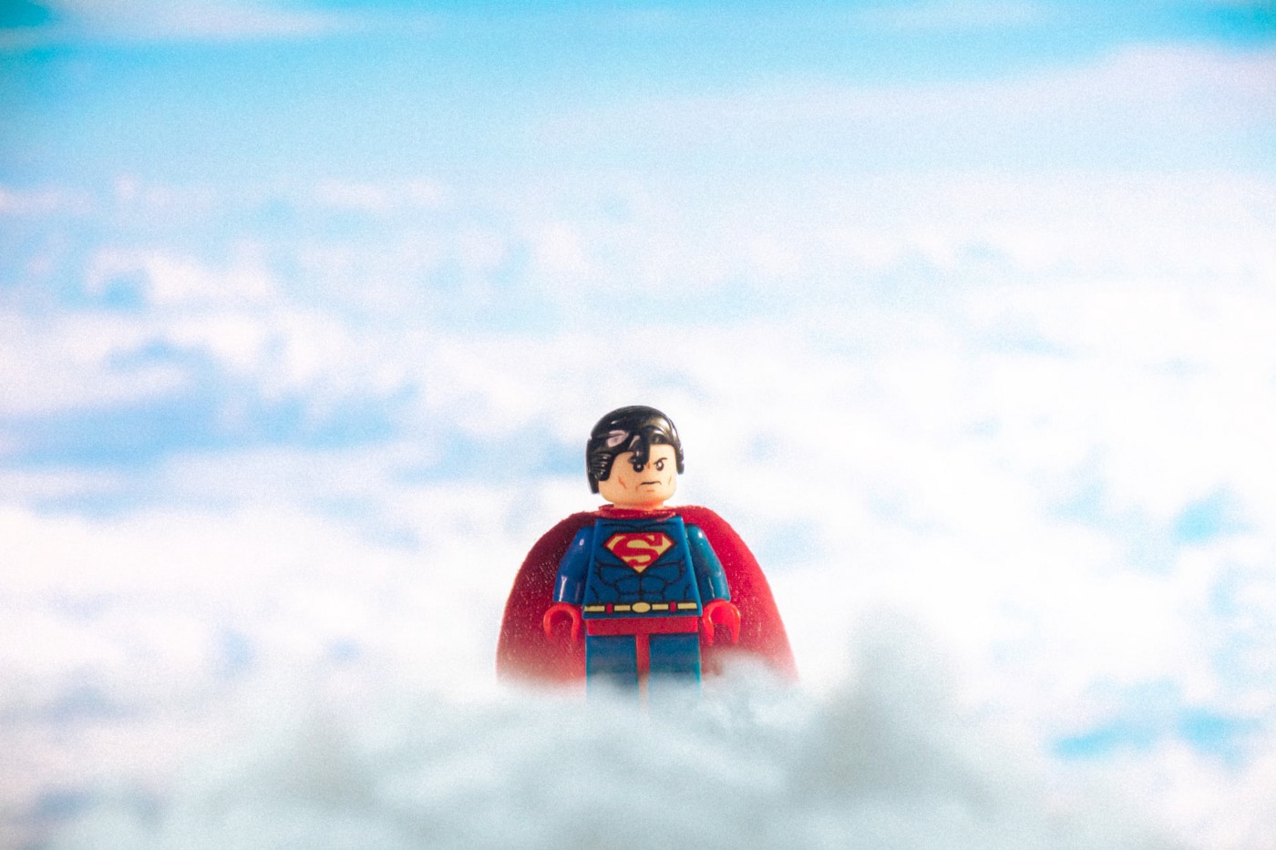 A lego Superman surrounded by white clouds, as if he's hanging up there watching over the earth.