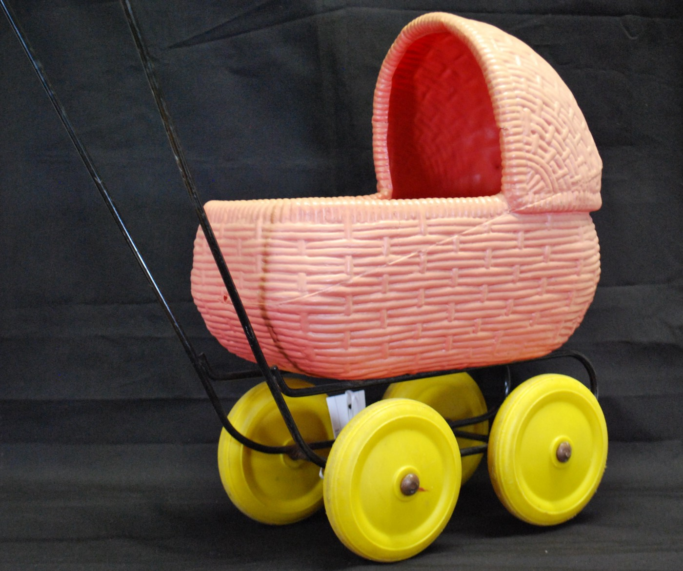 Image shows a pink plastic woven-look toy pram with yellow wheels. The pram is on a black frame with a handle to pushed by children.