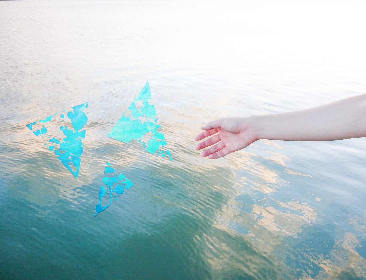 A photo of a hand extending to water with three abstract triangles.
