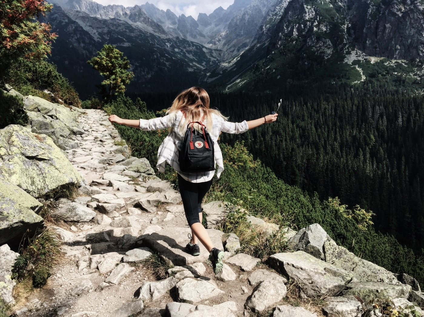 A woman wearing a backpack on a hike.