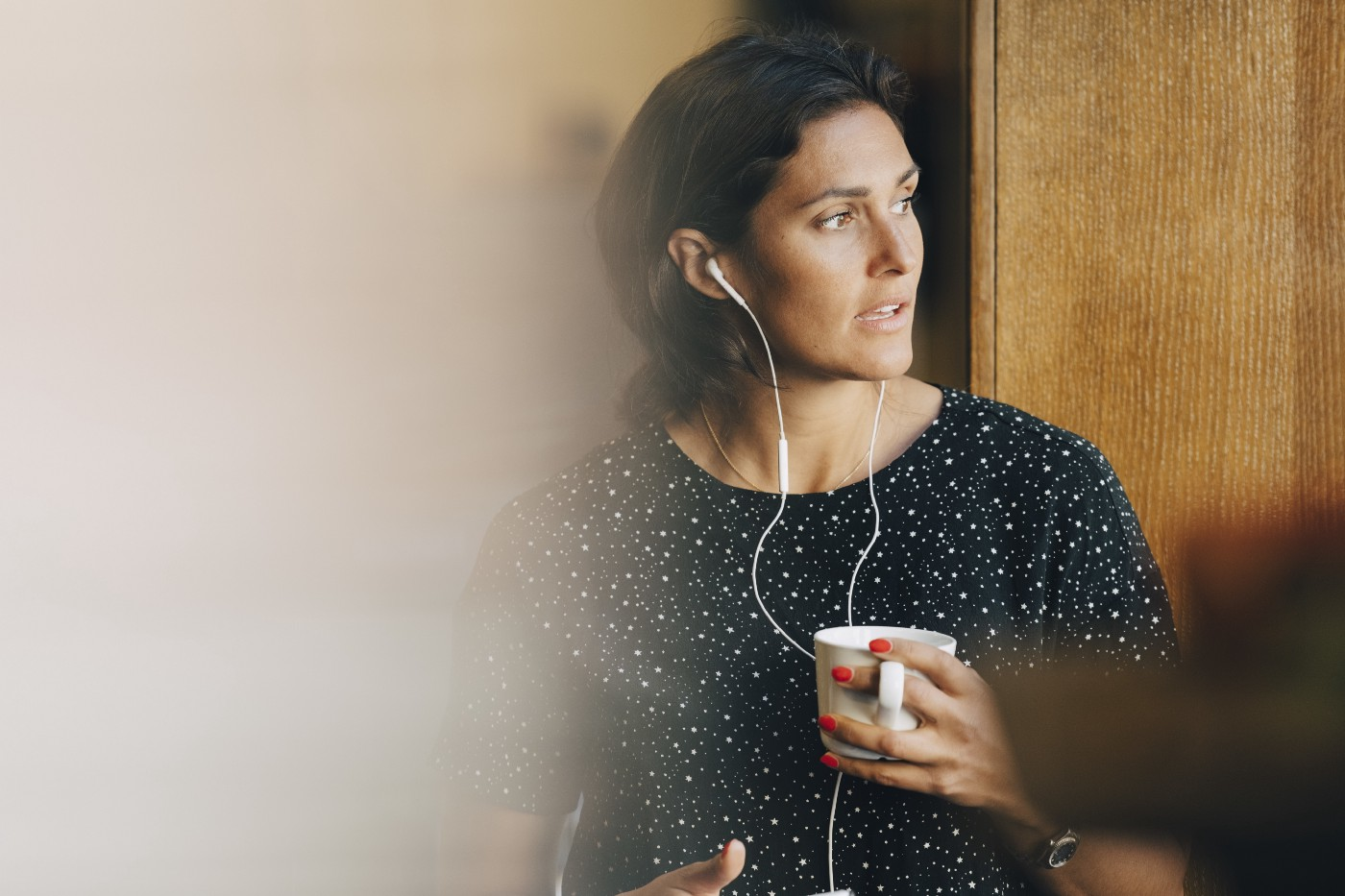 A businesswoman holding a coffee cup while talking on earphones in office