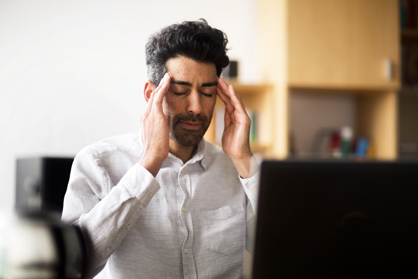 A man closes his eyes and massages his temples to relieve stress in front of his laptop.