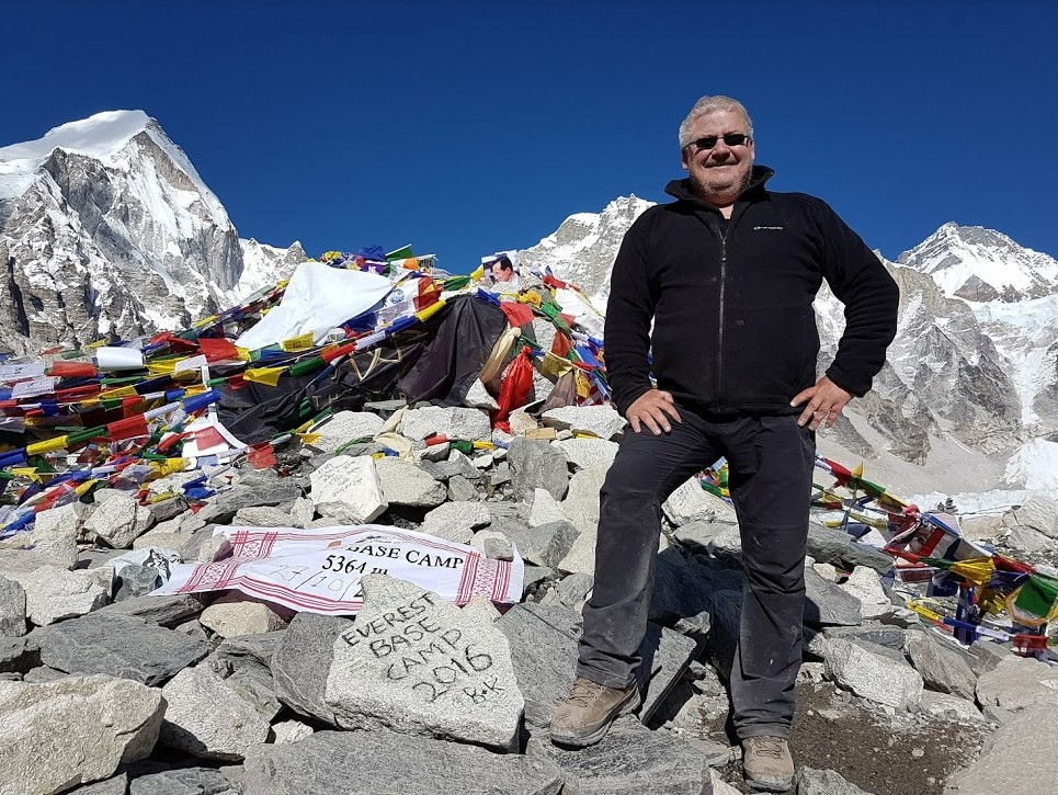 """Rocks draped with Buddhist Prayer Flags and a person standing beside a stone which has the words, """"Everest Base Camp 2016"""" inscribed on it."""