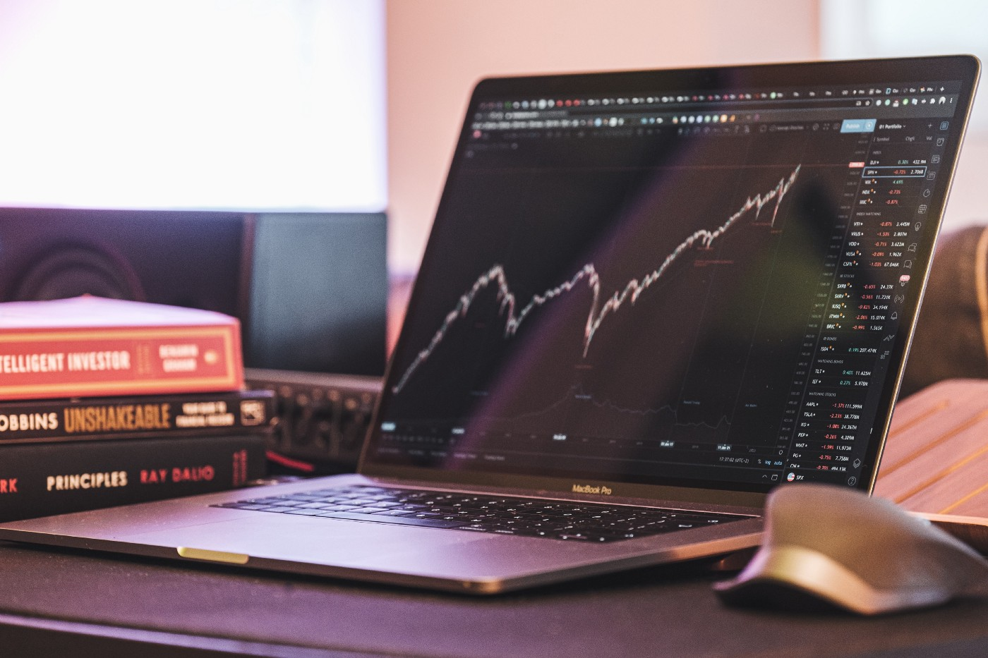 A laptop and investing books