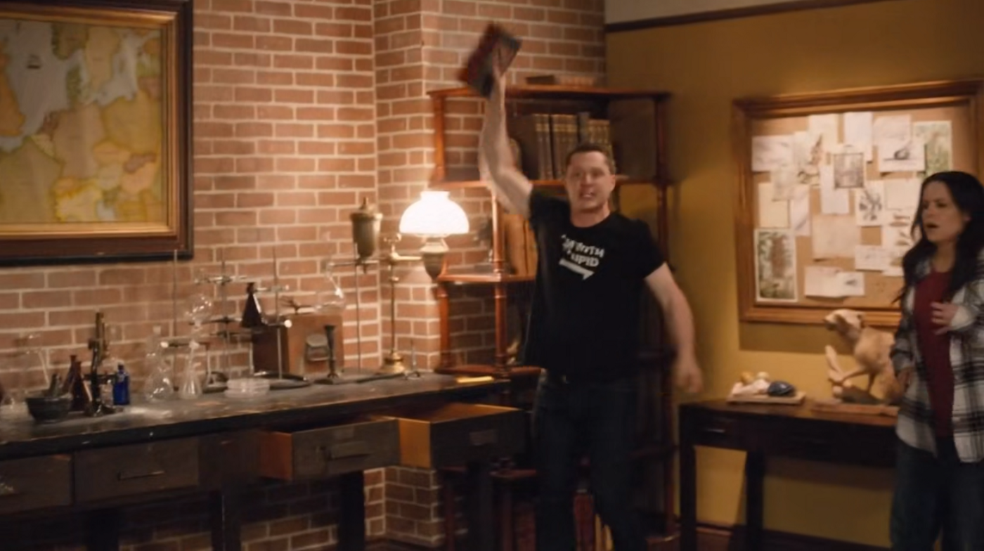 A man triumphantly holds up a book that he's pulled from the bookshelf next to him