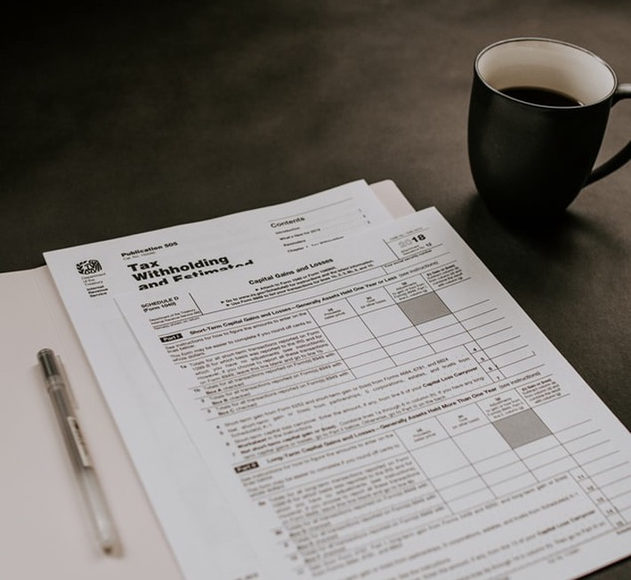 An image of tax retrun paperwork and a cup of coffee.