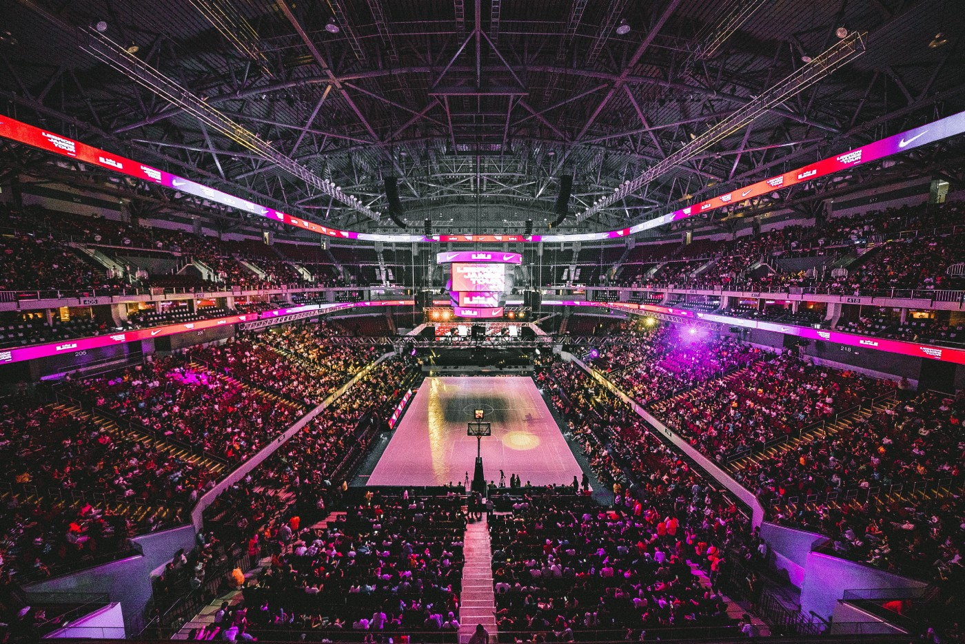 Fans pack a basketball arena in anticipation of an upcoming game.
