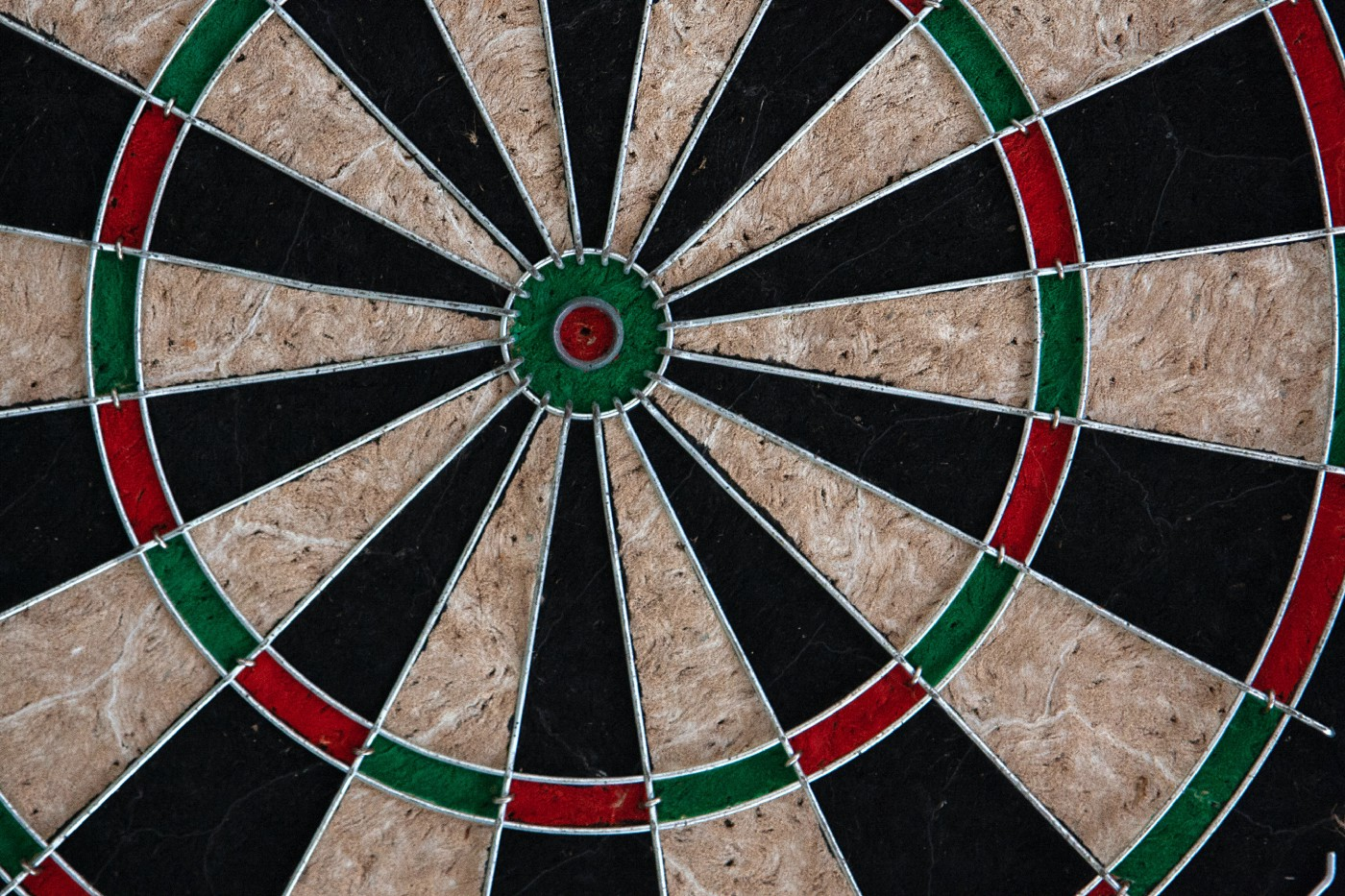 A close-up photo of a dartboard. Photo by Karen Laårk Boshoff at https://www.pexels.com/photo/black-red-and-white-round-decor-6758919/.