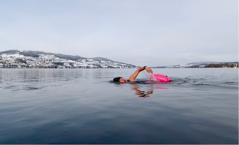 Female swimming front crawl in lake with snow on the surrounding hills.