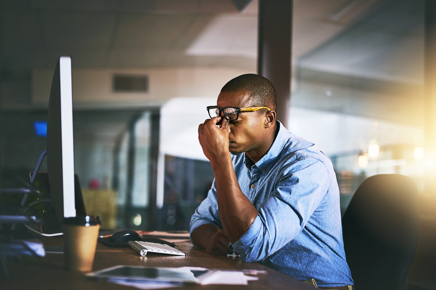 A photo of a frustrated entrepreneur sitting at his desk, pinching his eyelids.