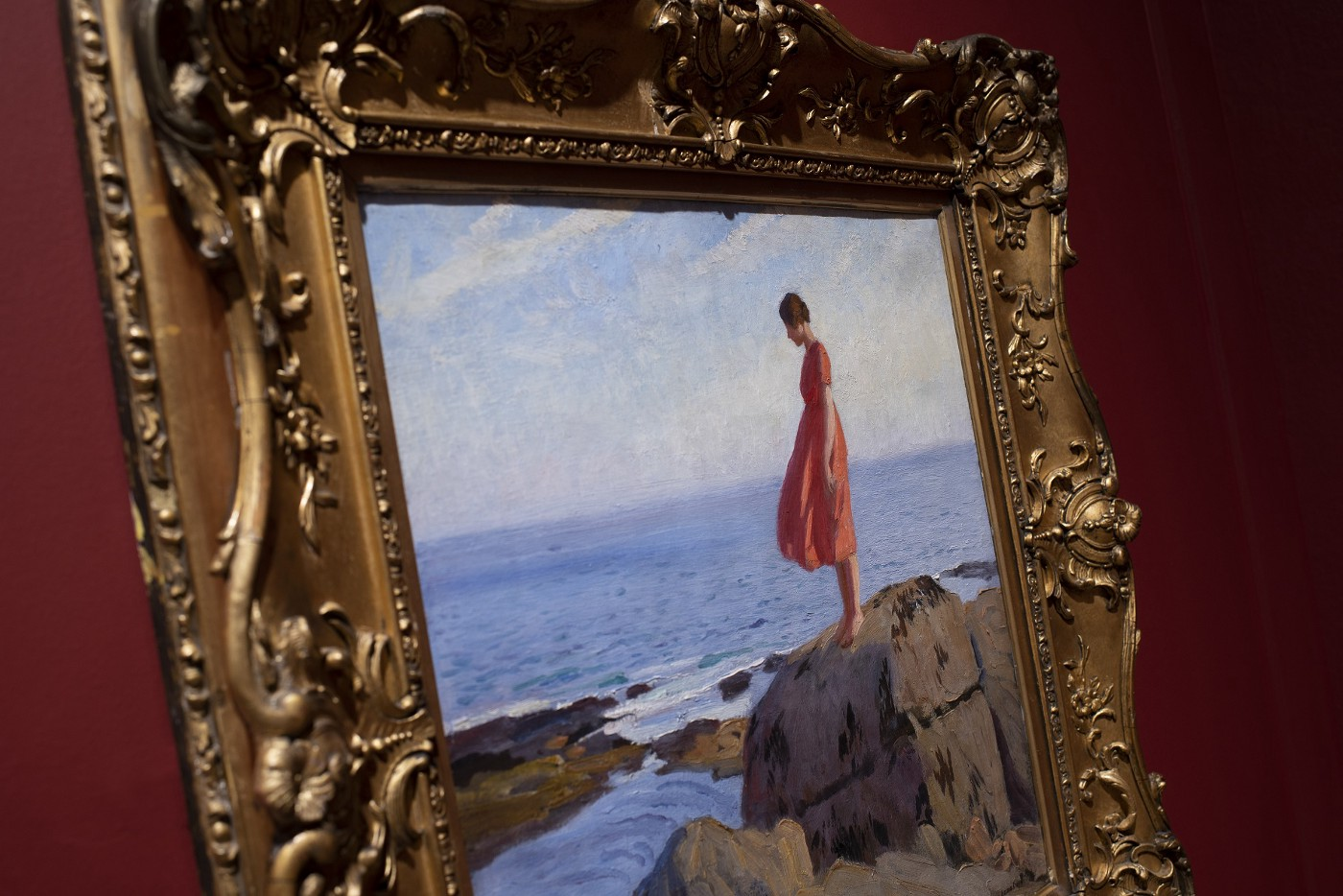 Close up of gold frame against a red wall, showing a painting of a woman in a red dress on a rock, looking out to sea