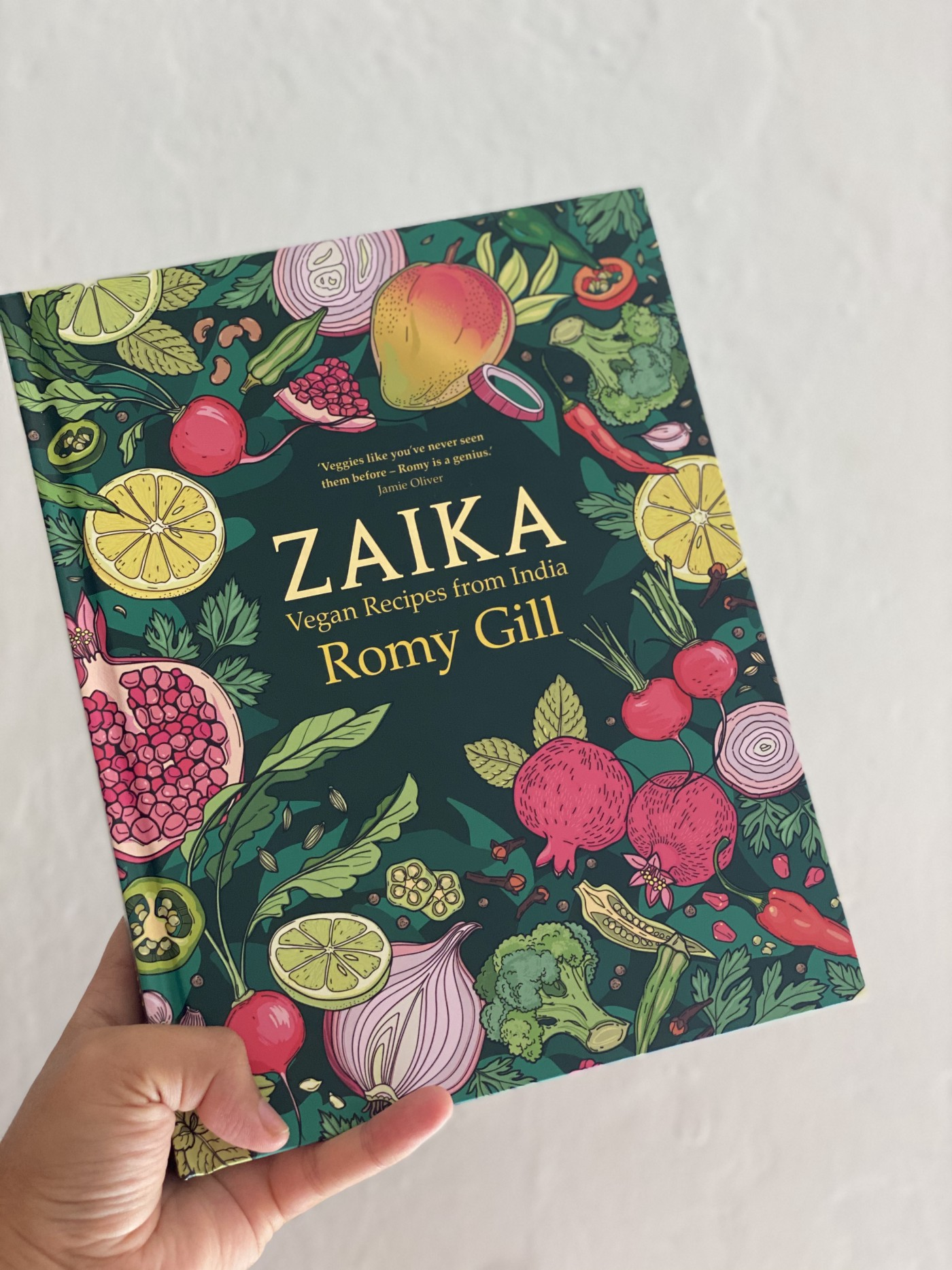 "A hand holding the book ""Zaika"" by Romy Gill, which has illustrations of various vegetables and fruits on a dark green cover"