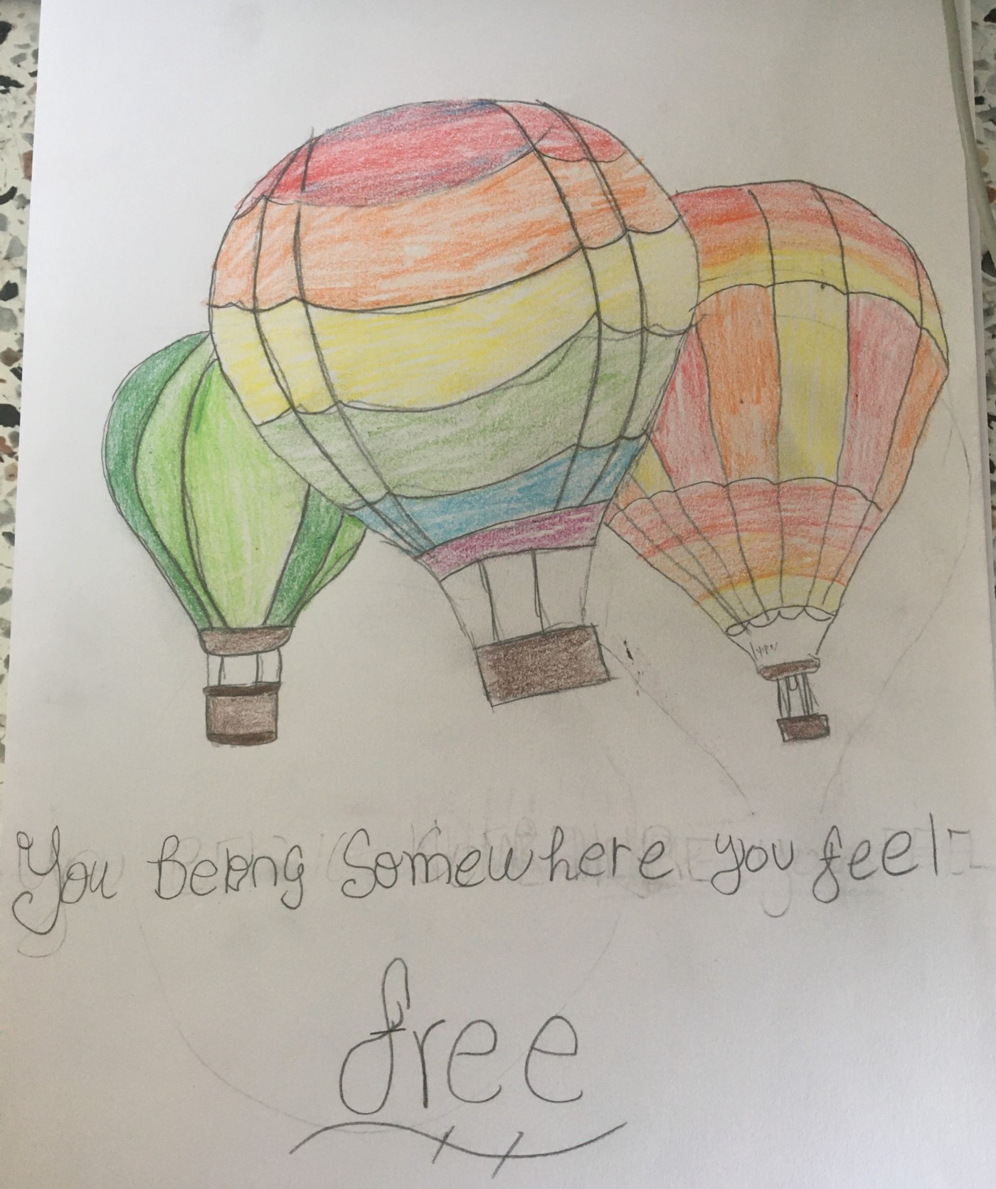 """This artwork is a coloured pencil drawing that features rainbow-coloured hot air balloons, and reads: """"You belong somewhere you feel free."""""""