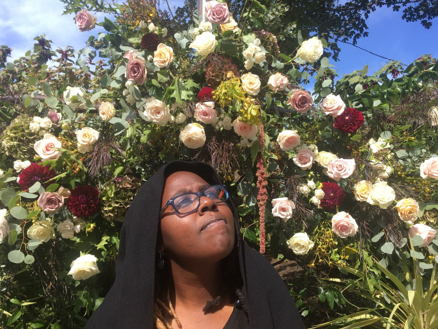 Author standing beneath a bush of roses.