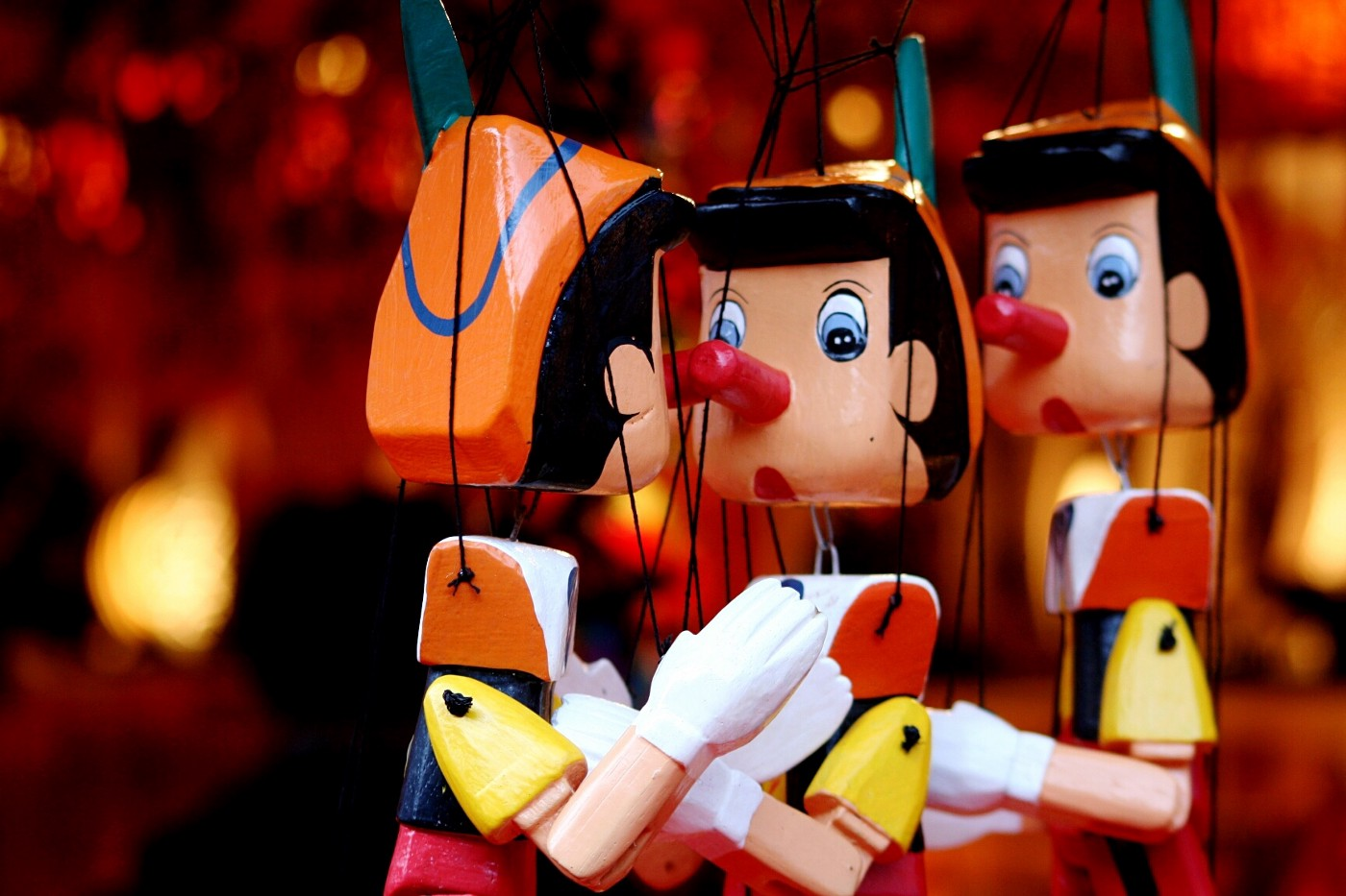 A close-up of 3 Pinocchio string puppets.