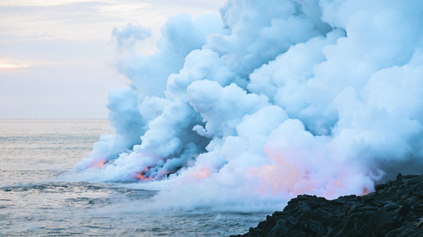 Lava pouring into ocean; forming new land while producing lots of billowing clouds
