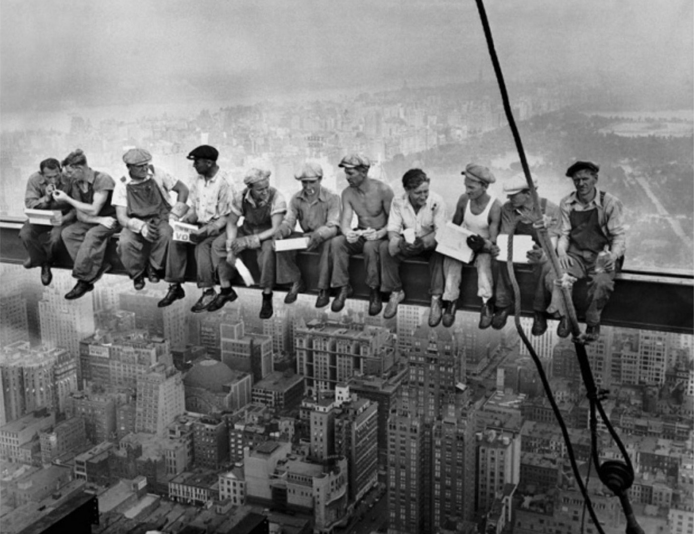 Old photo of immigrants sitting and eating lunch high up on a construction beam above New York City