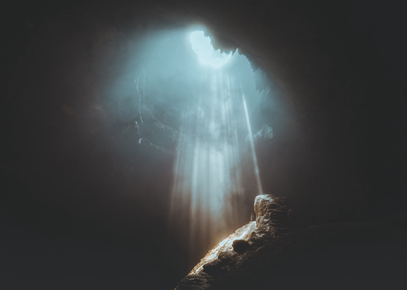 A photo of a cave. A stream of light is shining down on the opening of the cave, revealing its rocky bottom.