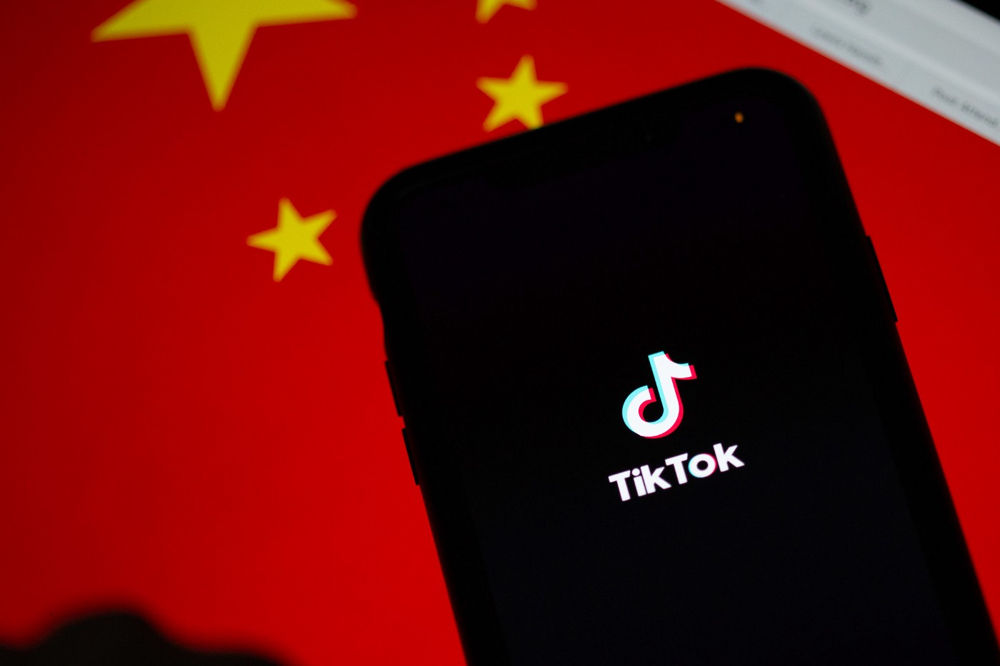 A phone displaying the TikTok logo is placed in front of a Chinese flag.