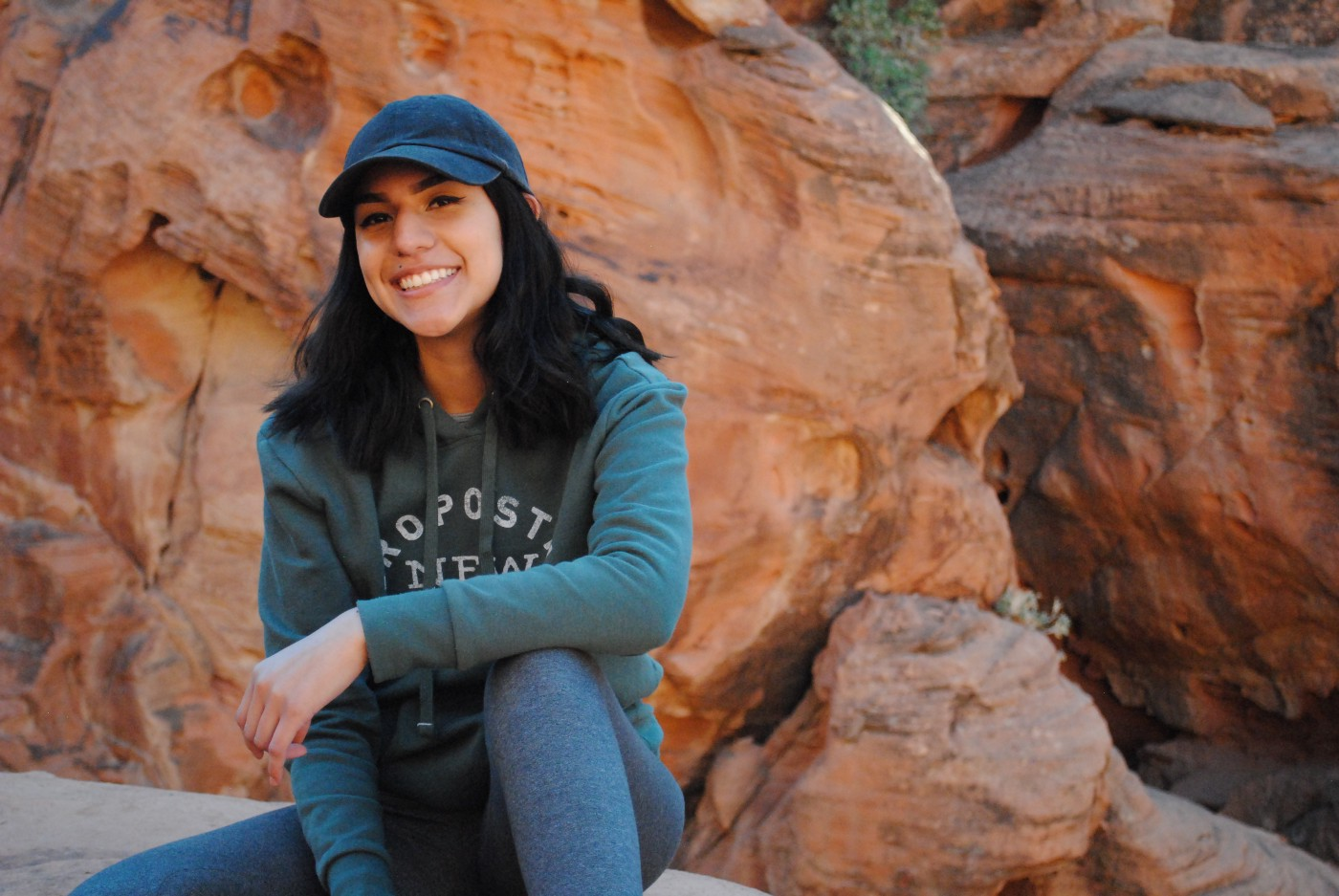 Lory sits in front of red boulders