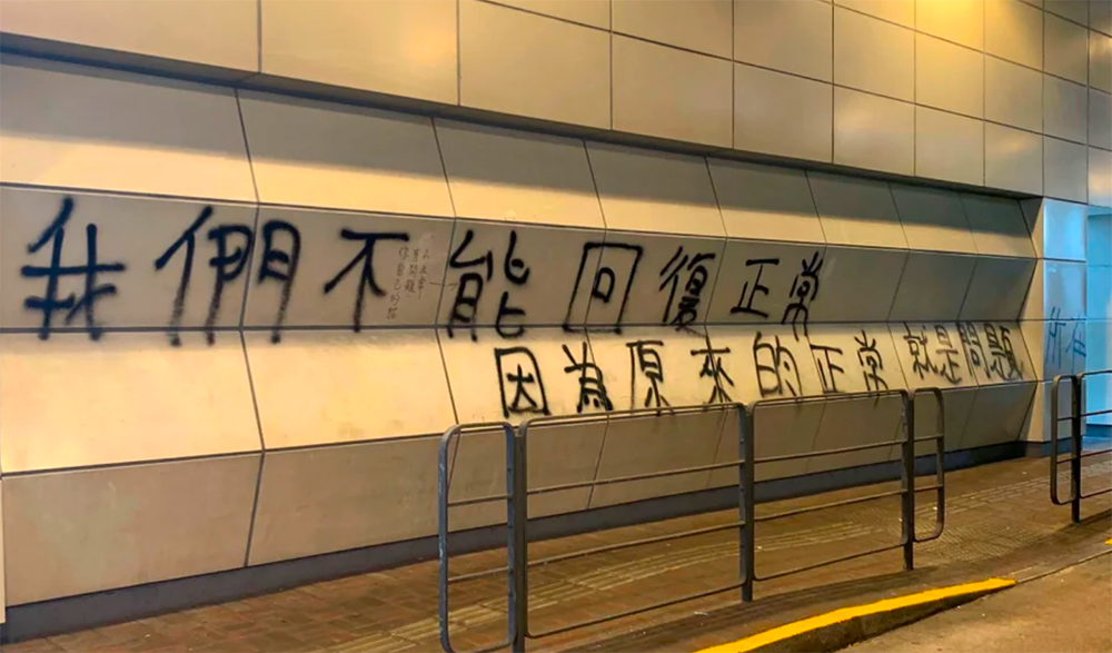 "A graffiti on a wall that reads in Chinese: ""We can't return to normal because the normal we had was precisely the problem"""
