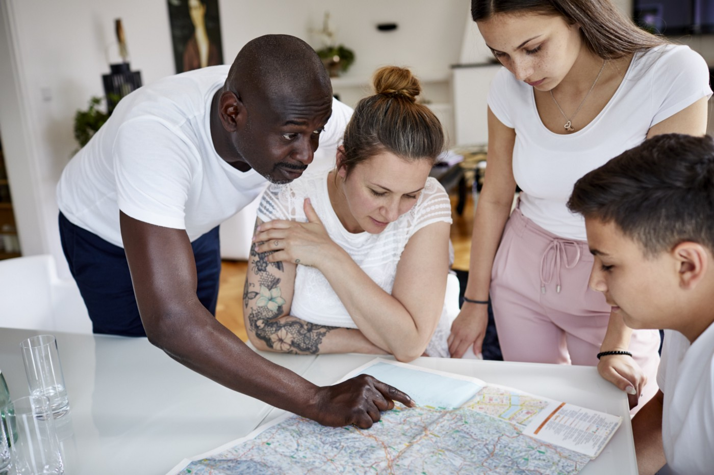 A family looks at a map at home.