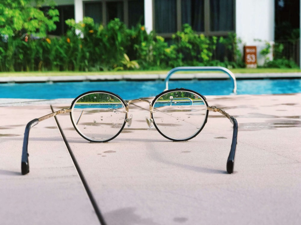 looking at a pool from a round lenses glasees in a summer atmosphere, vegetation in the background