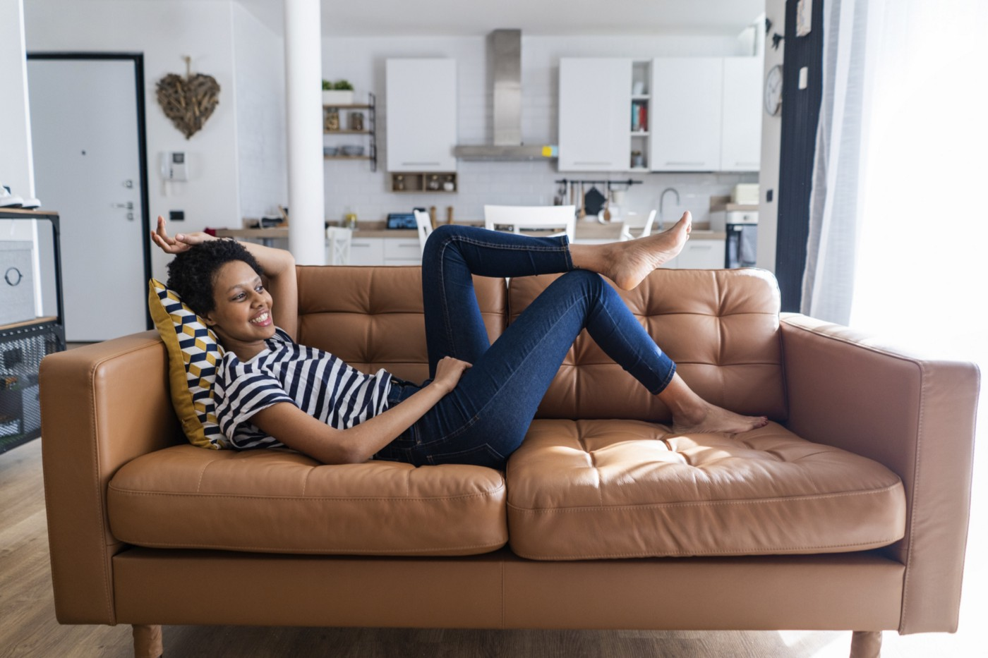 Black woman relaxing at home on her sofa.