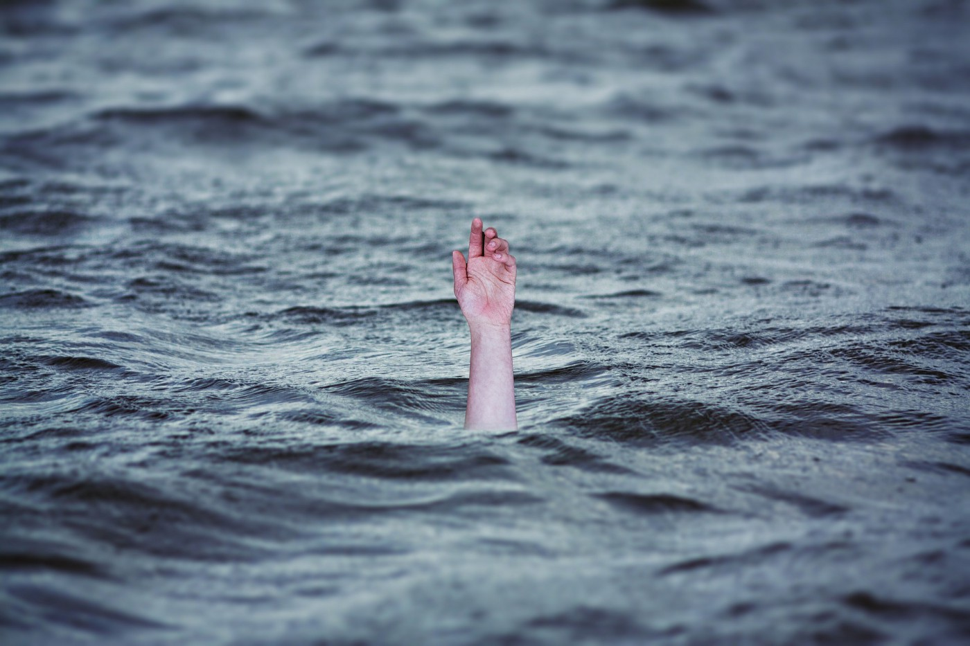 Photo of a hand reaching up out of the blue sea, as if someone is drowning.