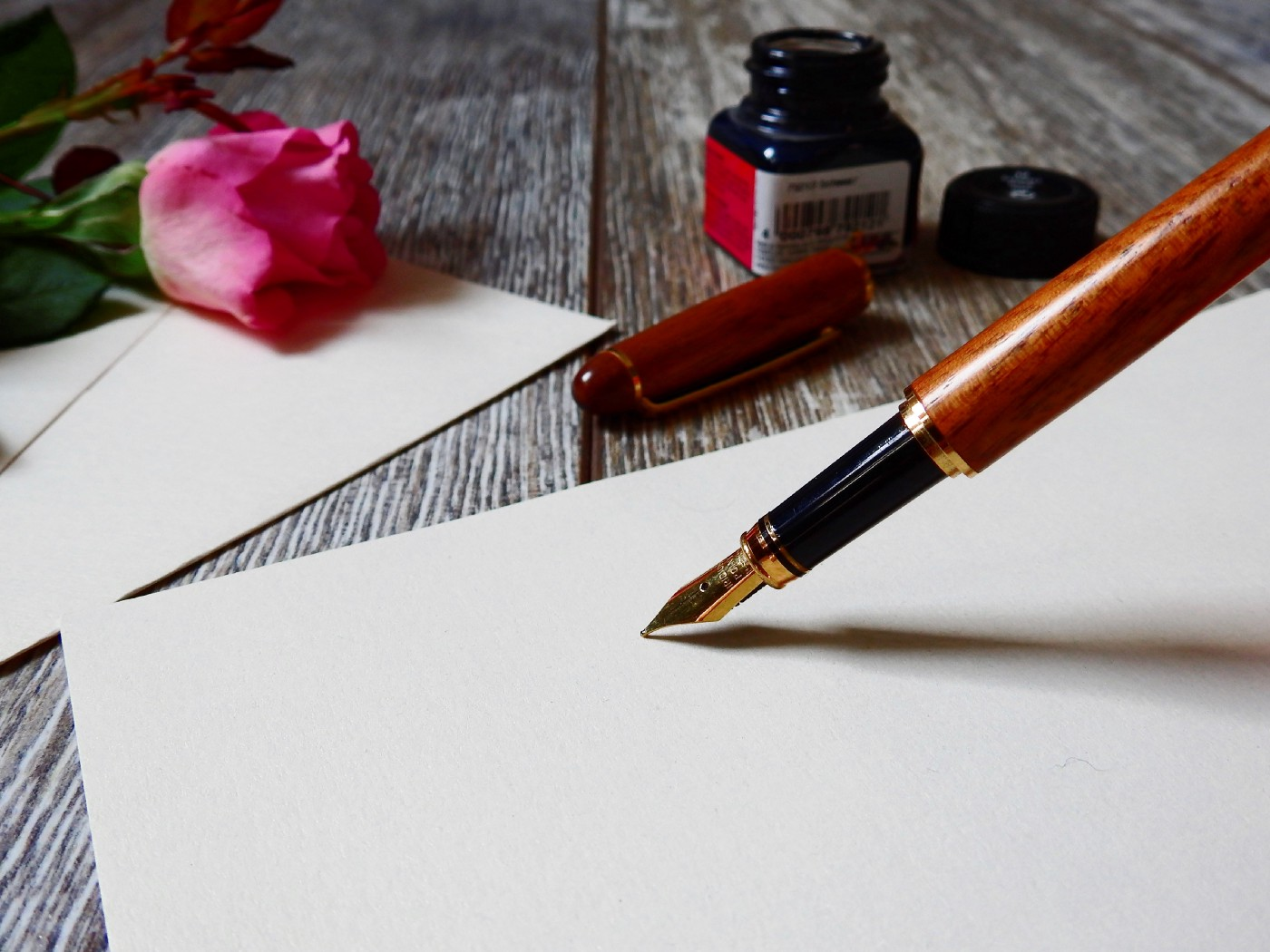 Image of a pen writing on paper.
