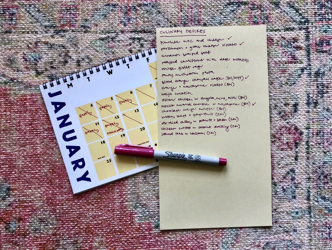 "A handwritten list of ""Culinary Desires"" and a pen on a woven rug next to a calendar turned to the January page."