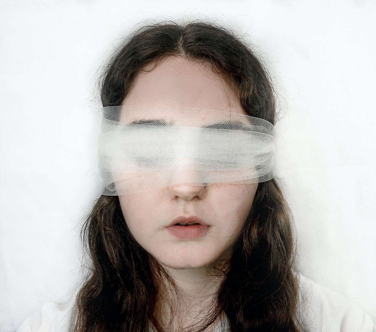 a White woman's face, eyes closed, wearing a white, gauzy blindfold