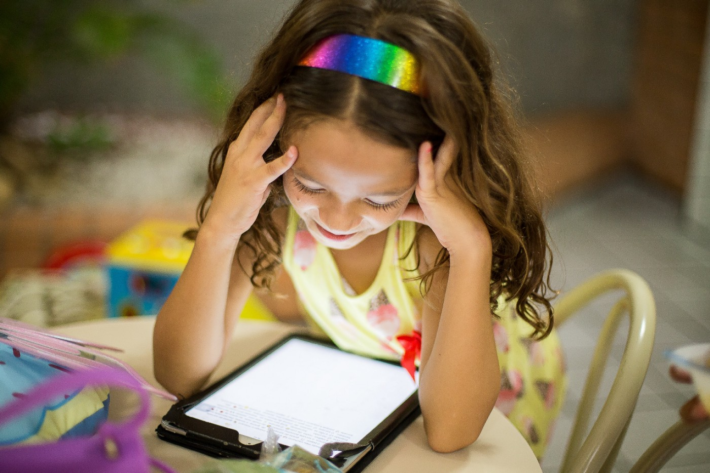 Girl wearing a rainbow headband sitting and looking and down at a tablet device.