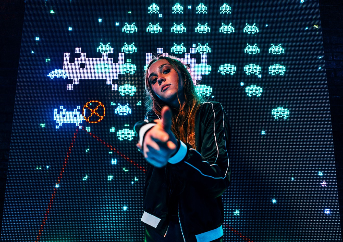 Girl making finger-guns at the camera, standing in front of a screen showing gameplay from 'Space Invaders'
