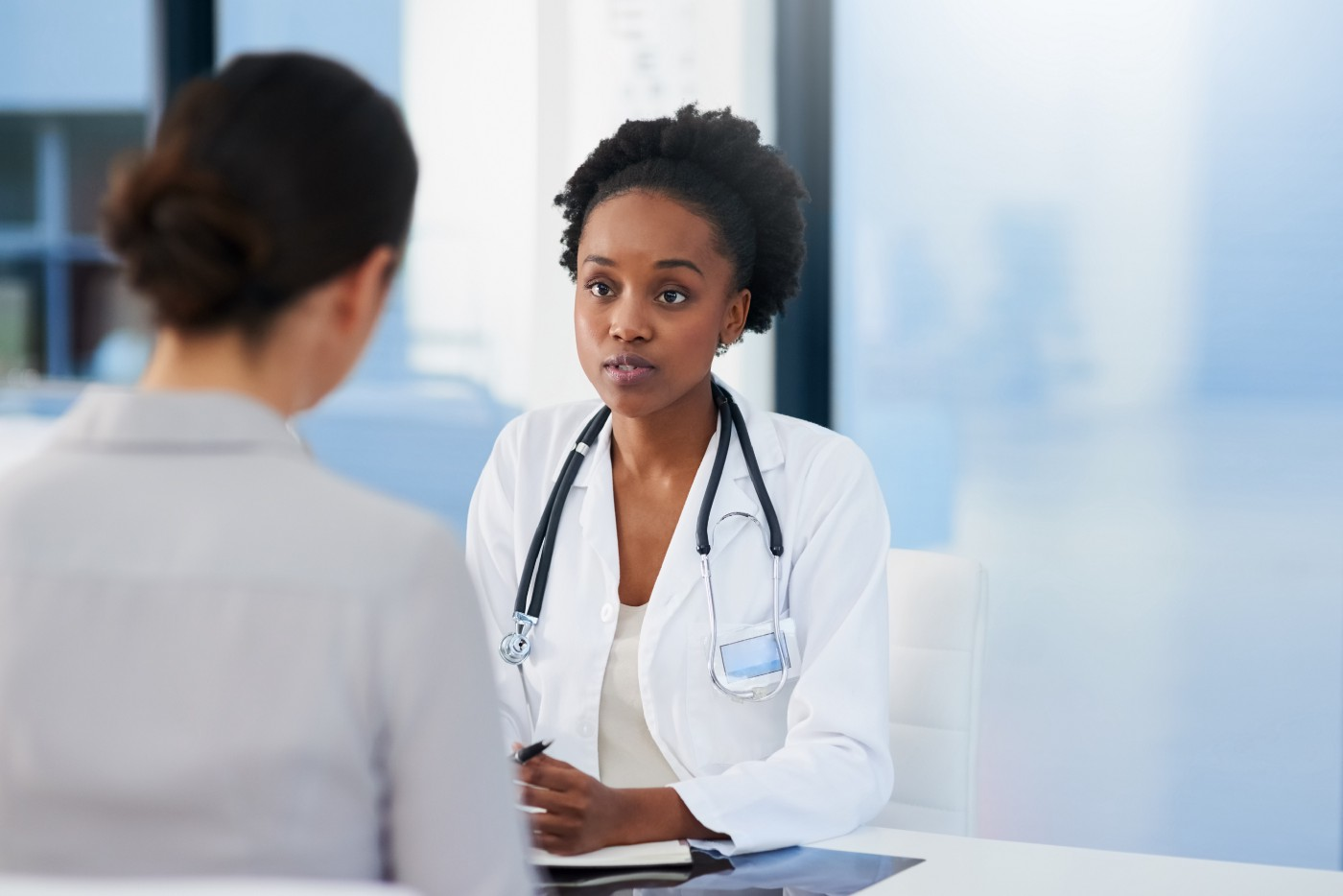 A cropped shot of a doctor, who is a woman of color, talking to a patient in her office.
