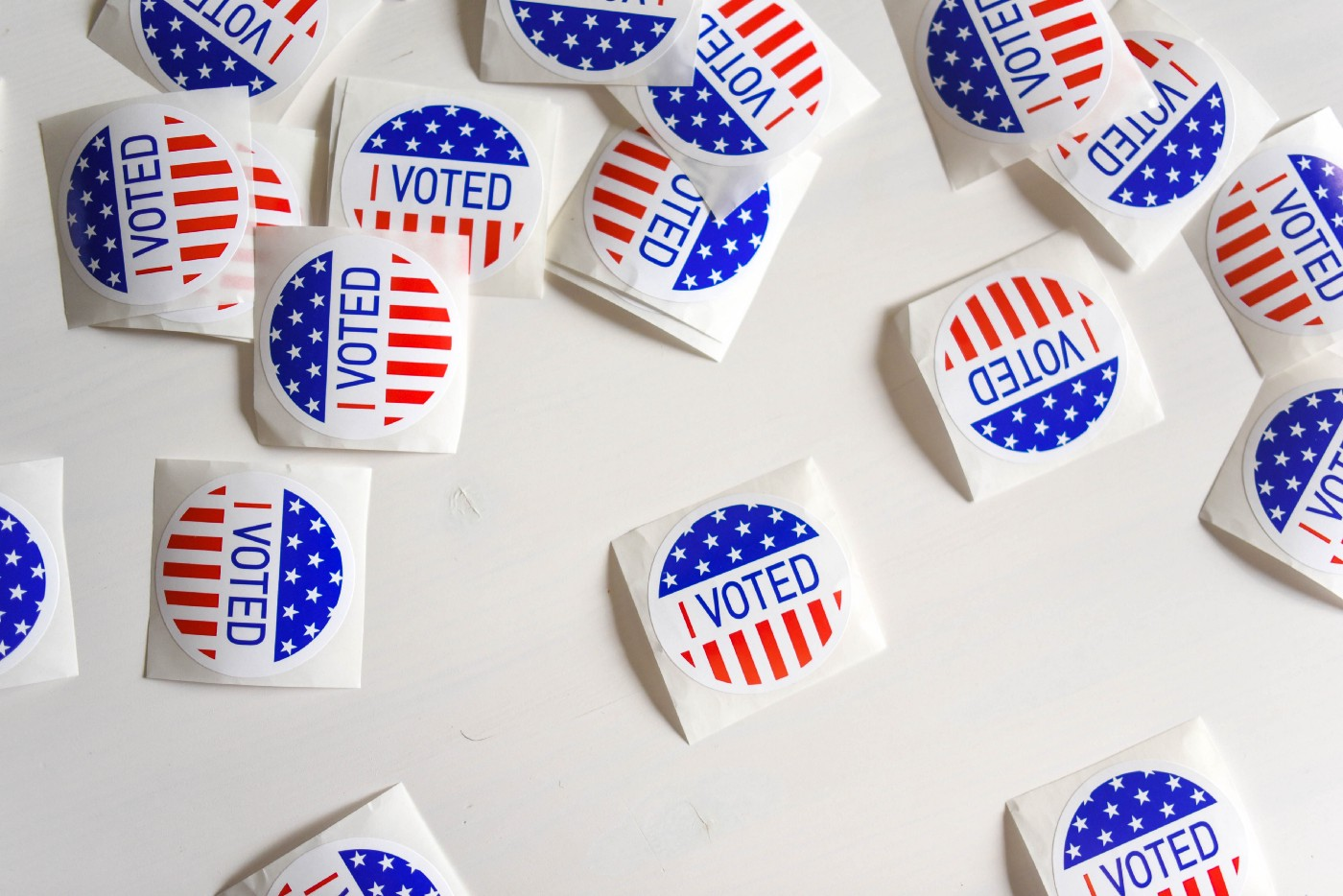 """I voted"" stickers donning US stars and stripes, scattered across a white tabletop"