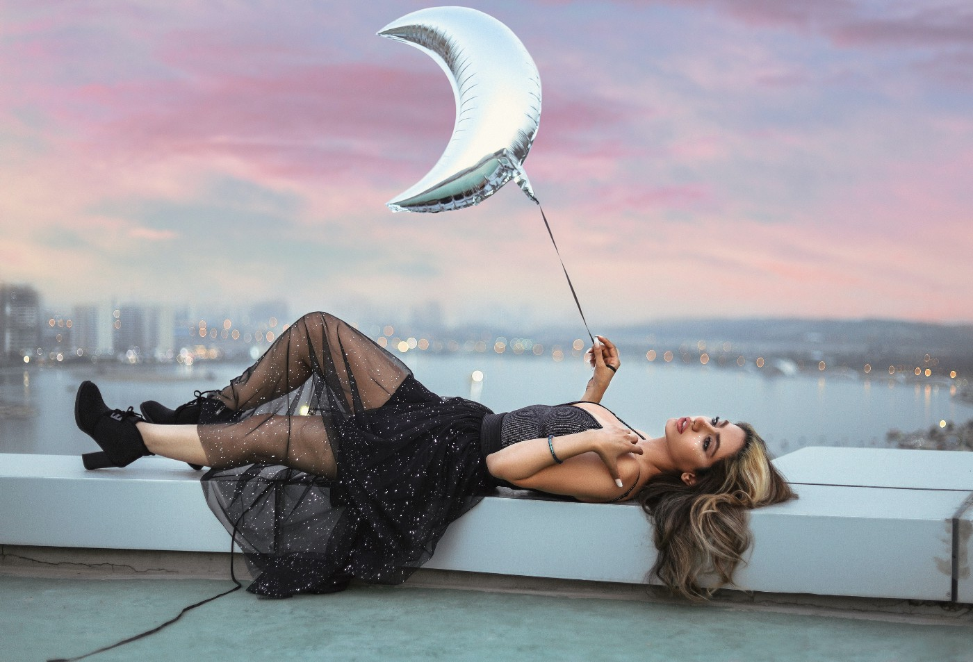 Woman in black dress laying down next to purple sky, and holding onto a moon shaped silver balloon