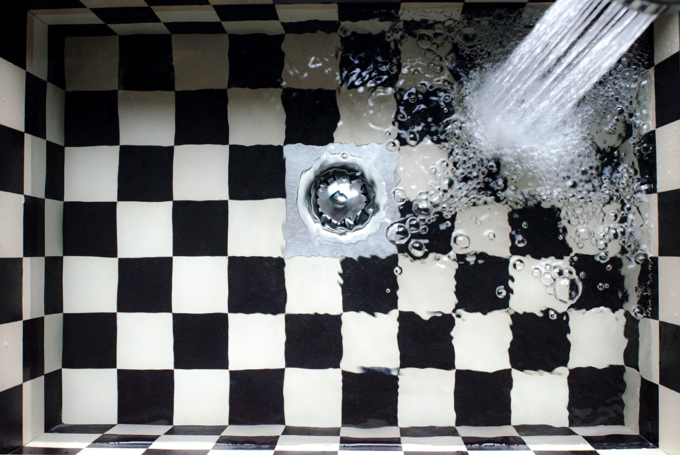 Water going down the drain in a black-and-white tiled shower.