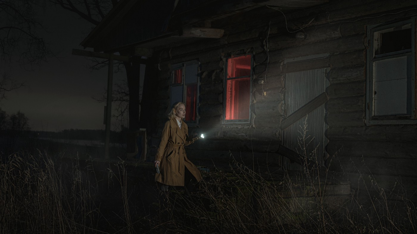 A woman investigates a house with a flashlight.