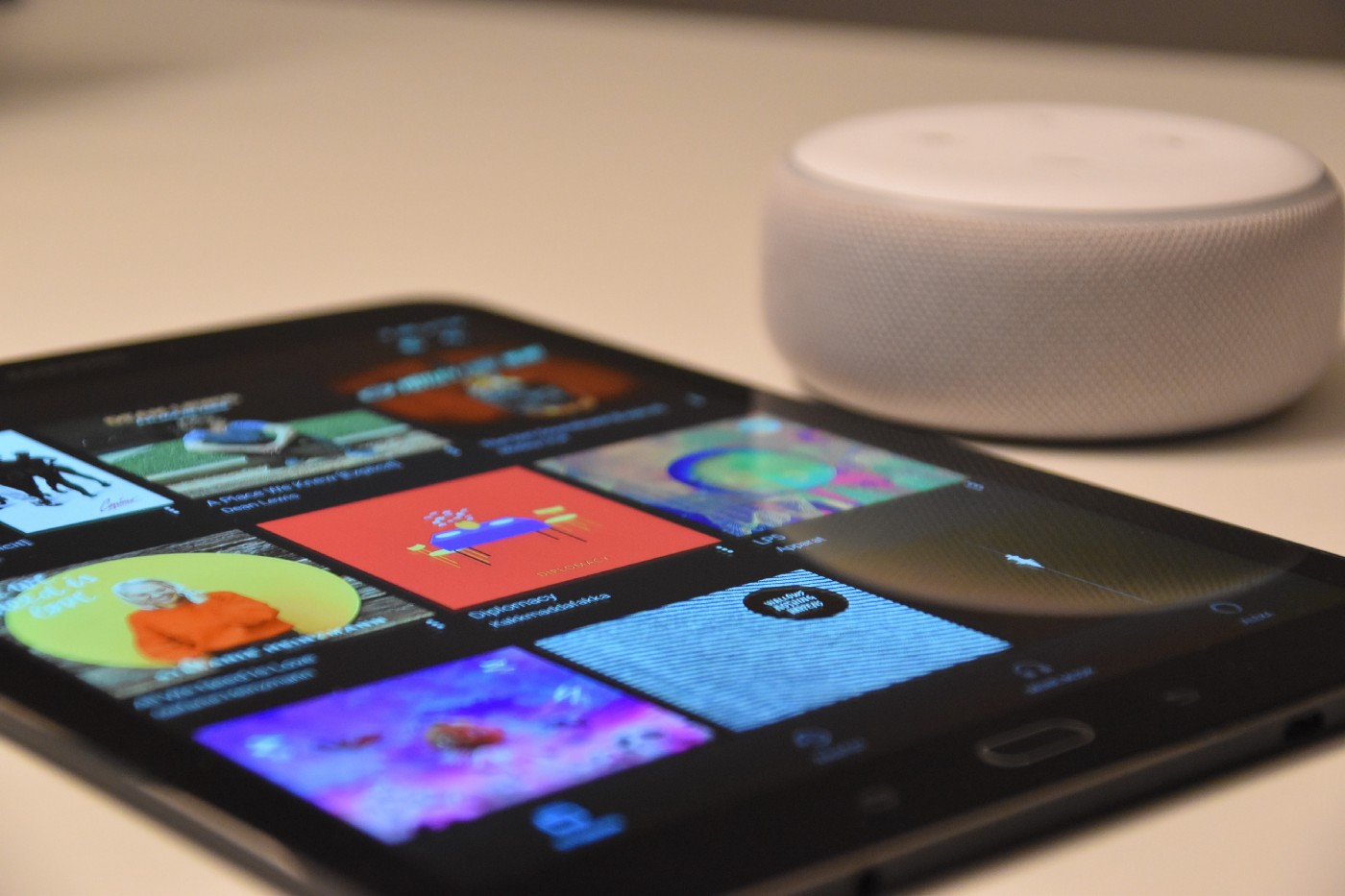 A close up of a tablet with an Amazon Echo Dot in the background.