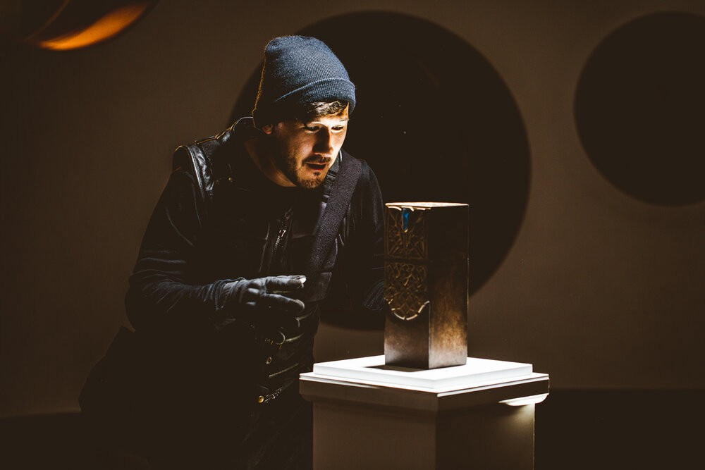 Mark Fischbach, in all black thief's gear, stands over a mysterious box, spotlit and sitting on a museum pillar.