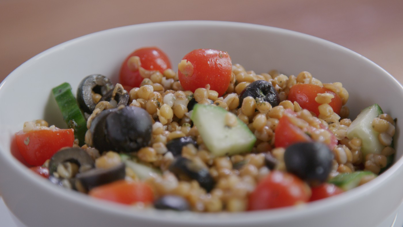 A close up of a wheat berry and lentil salad in a white bowl with cut cherry tomatoes, cucumbers and black olvies.