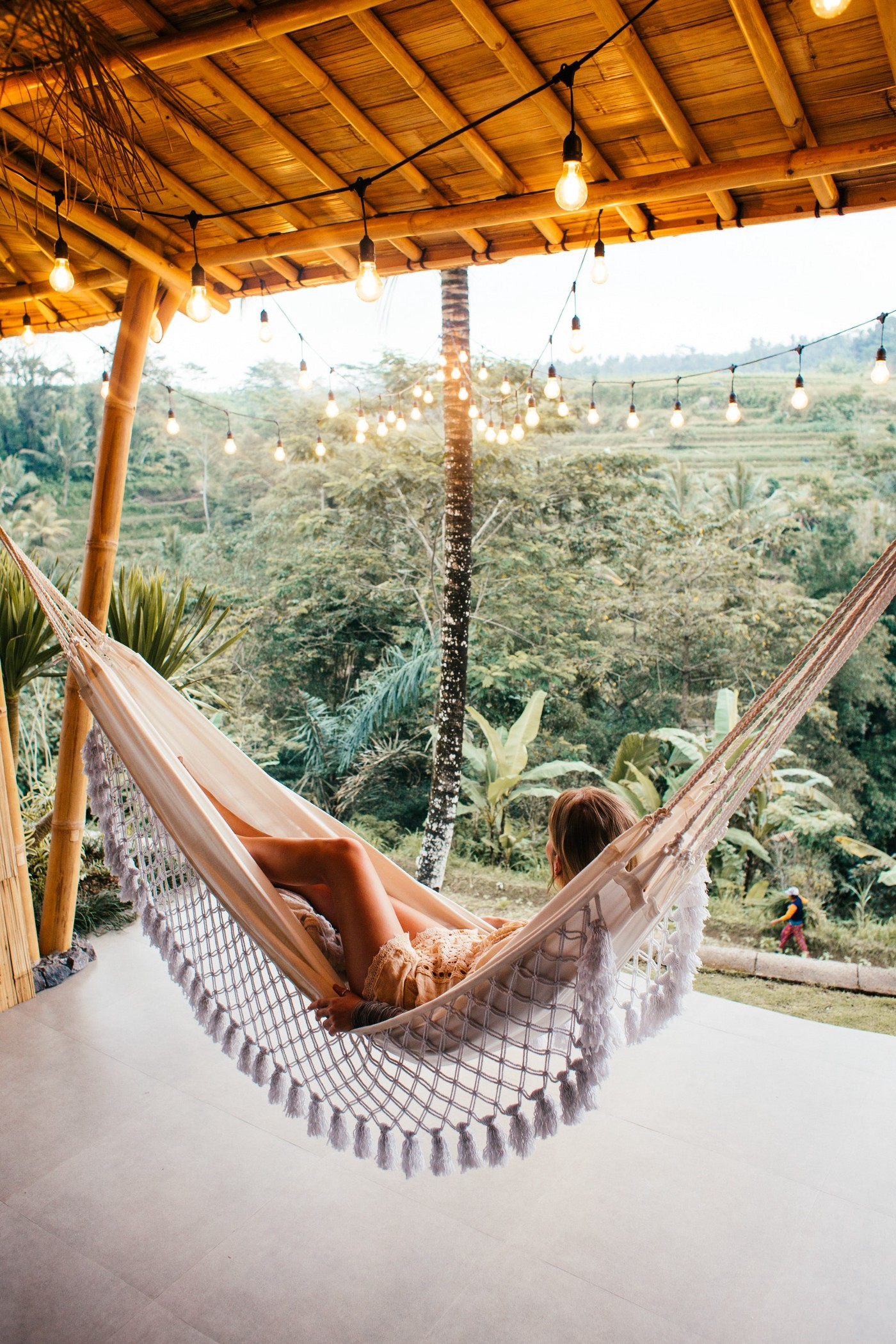 Woman laying in a hammock on a porch, overlooking nature.