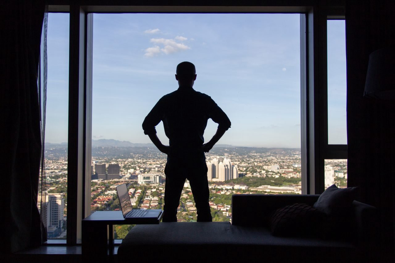 The silhouette of a man with his back turned standing at his full height with his hands on his hips, in front of a floor-to-ceiling window with a city view, with a chaise lounge sofa and an open laptop on a side table behind him.