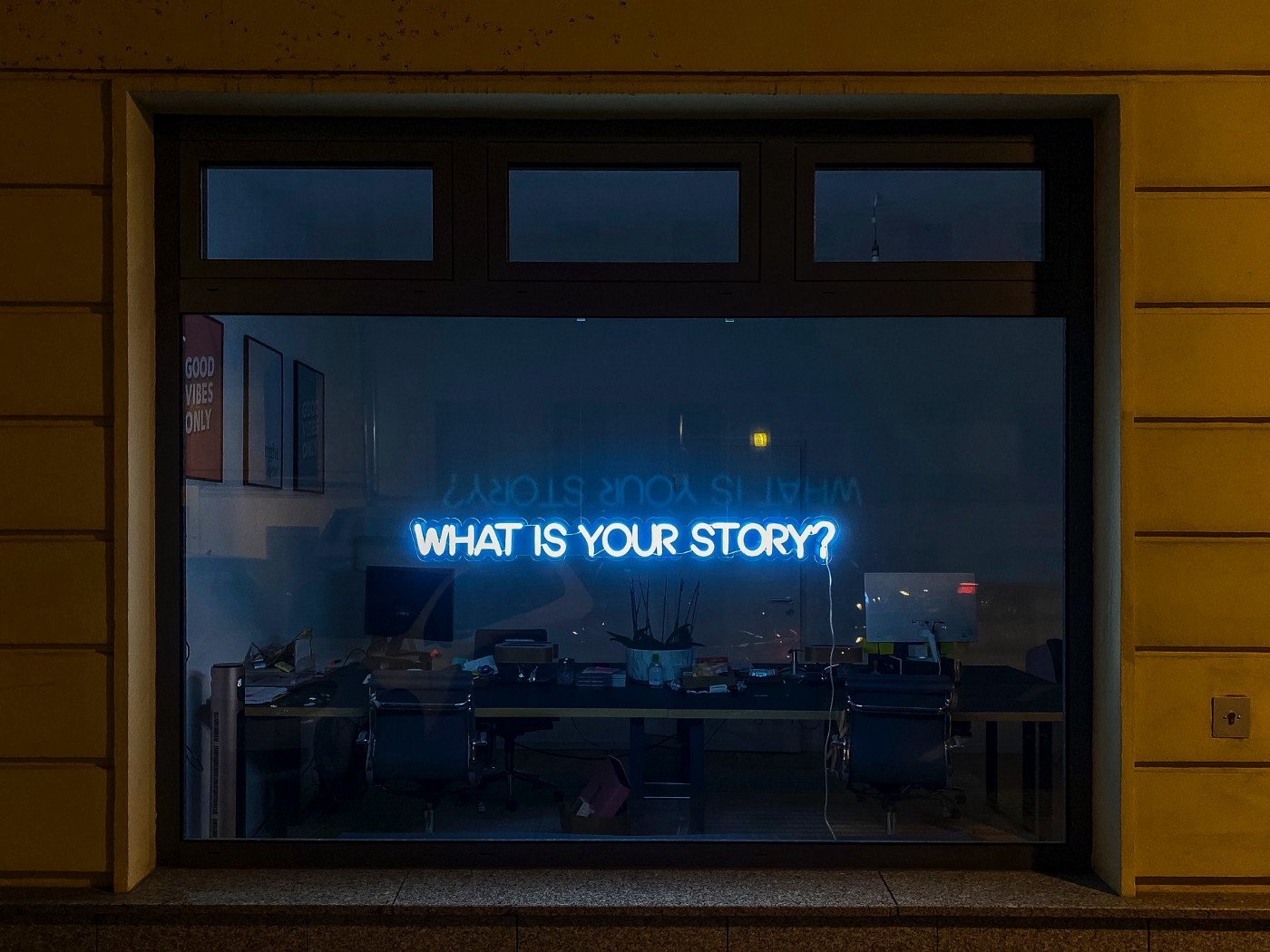 """A neon sign that reads """"What is your story?"""""""