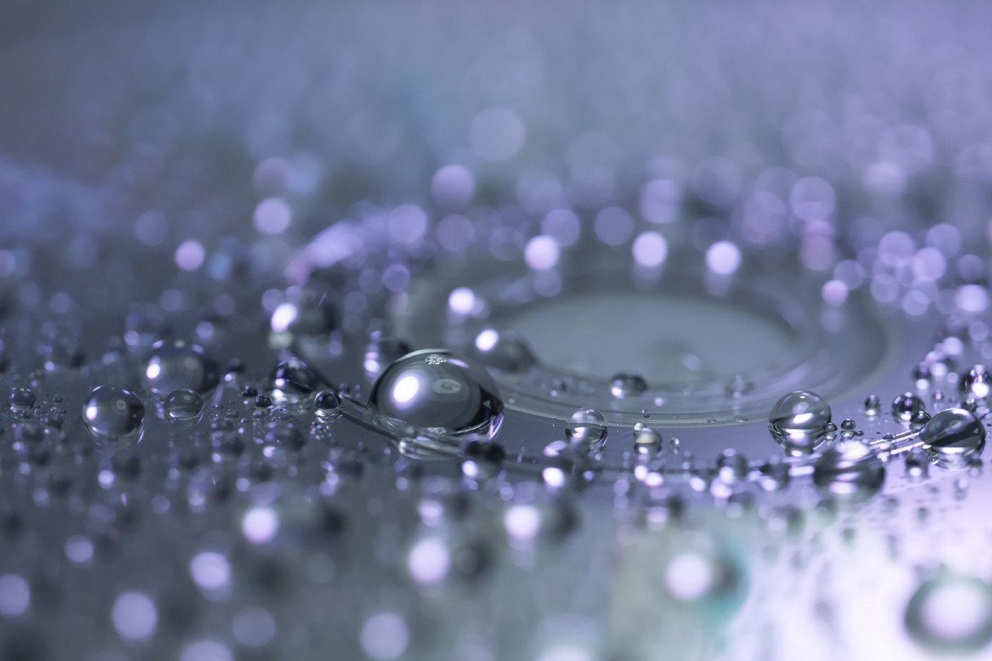 Shiny water droplets rest on a clear surface.